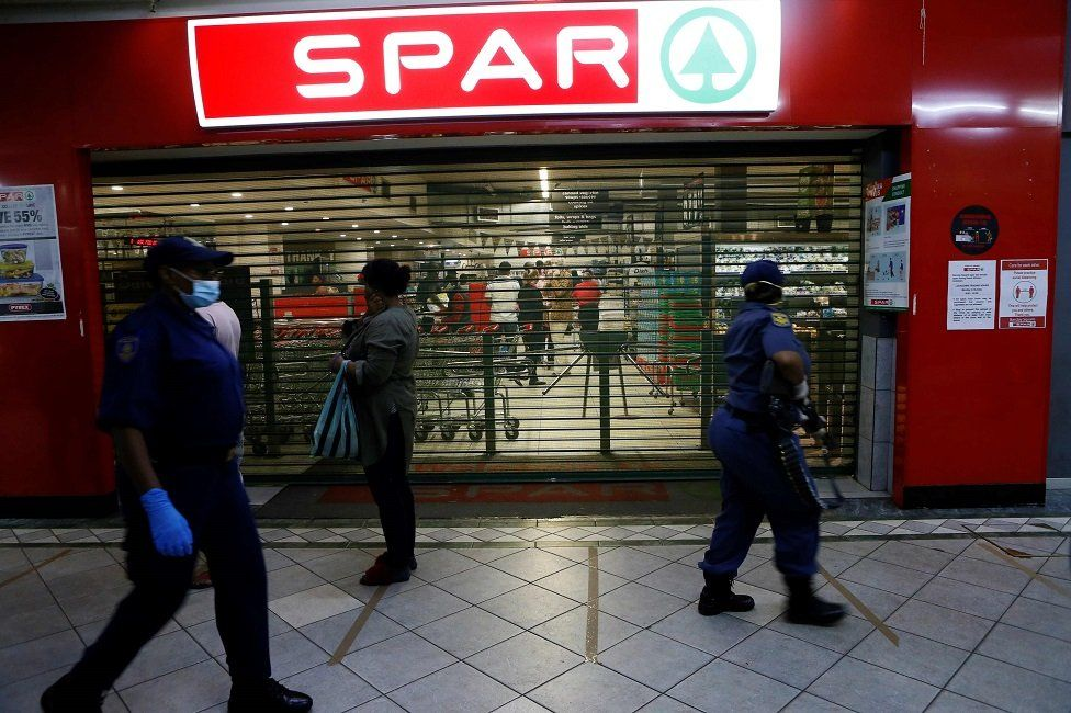 South African Police Service (SAPS) walk past shoppers queuing outside a food store during their operation in Sunnyside, Pretoria on April 7, 2020