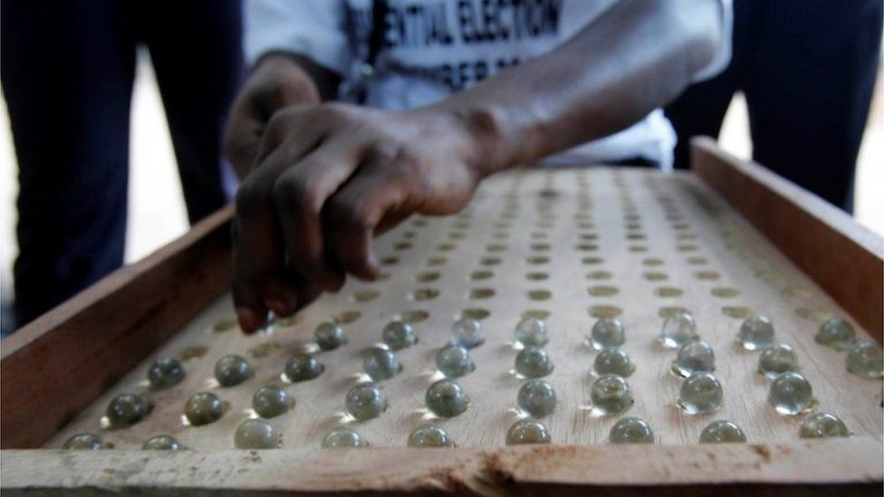 A poll worker counts votes cast by marbles after the close of voting during the presidential election in Banjul, Gambia, 1 December 2016.
