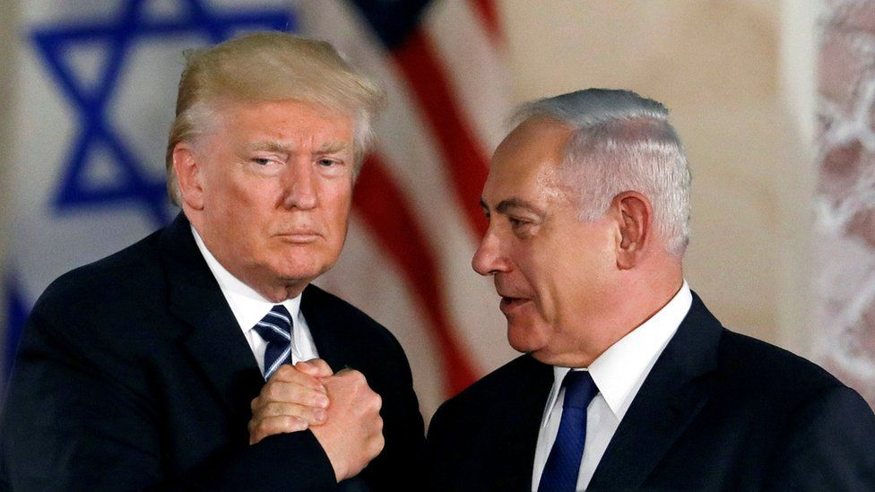 President Trump and PM Netanyahu shake hands in front of Israeli and US flags