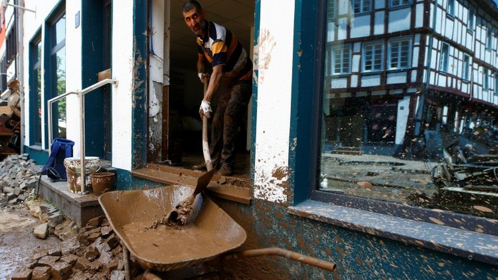 Man removes mud from property in Bad Muenstereifel