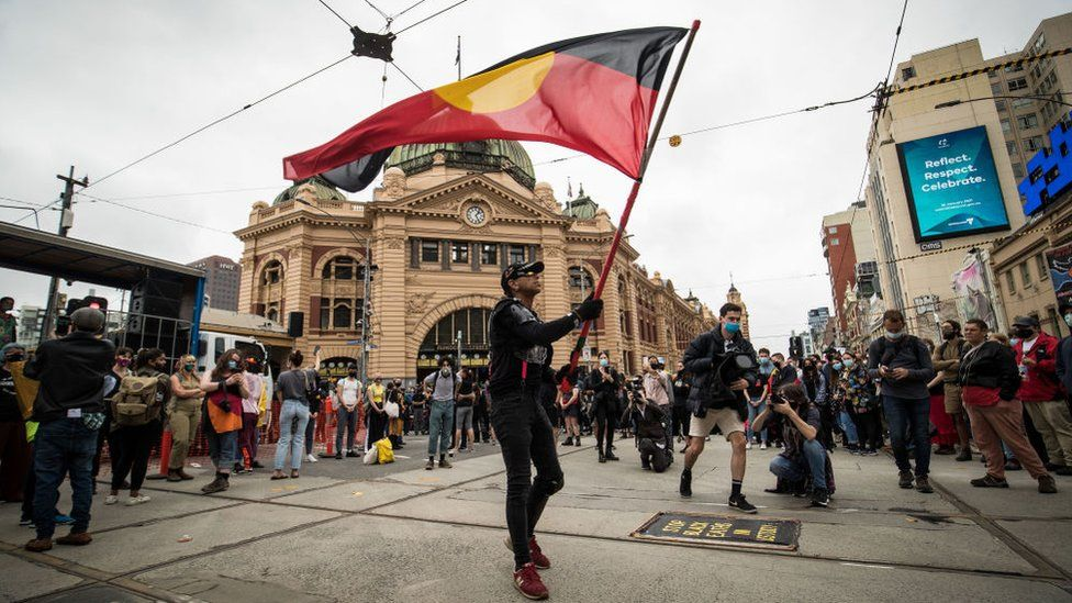A protester hold the Aboriginal flag in central Melbourne during a mass protest on Australia Day