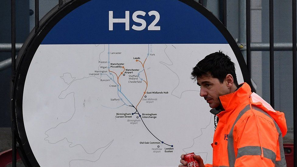 HS2 worker walks past map of HS2 route