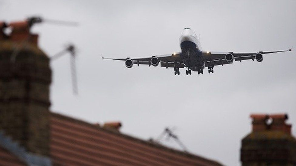 Plane flying over a house to Heathrow