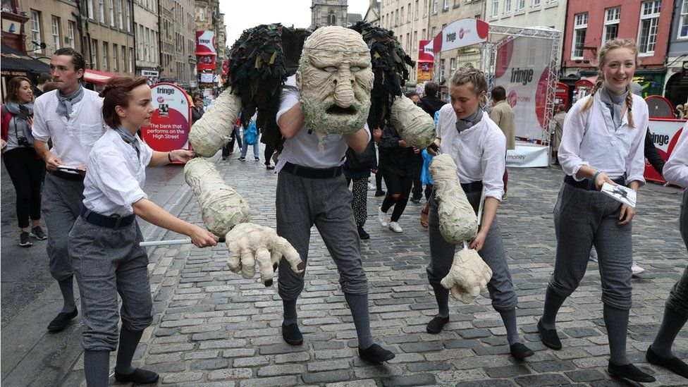 Edinburgh fringe performers put on a scene from their show Peer Gynt on the Royal Mile