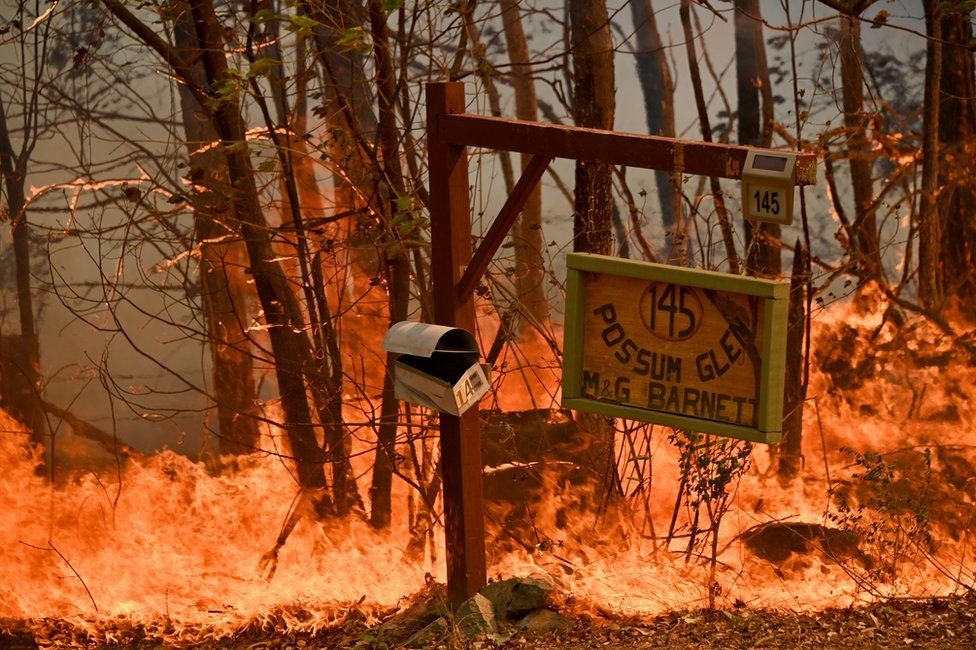 A mailbox and signpost burn amid heavy flames