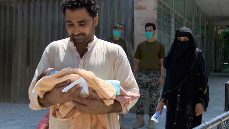An Afghan man walks with a baby at the Torkham crossing on the Pakistani-Afghan border