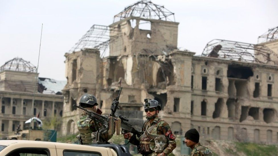 Afghan military soldiers stand stand alert at the entrance gate of the new parliament building after a rocket attack in Kabul, Afghanistan, Monday, March 28, 2016.