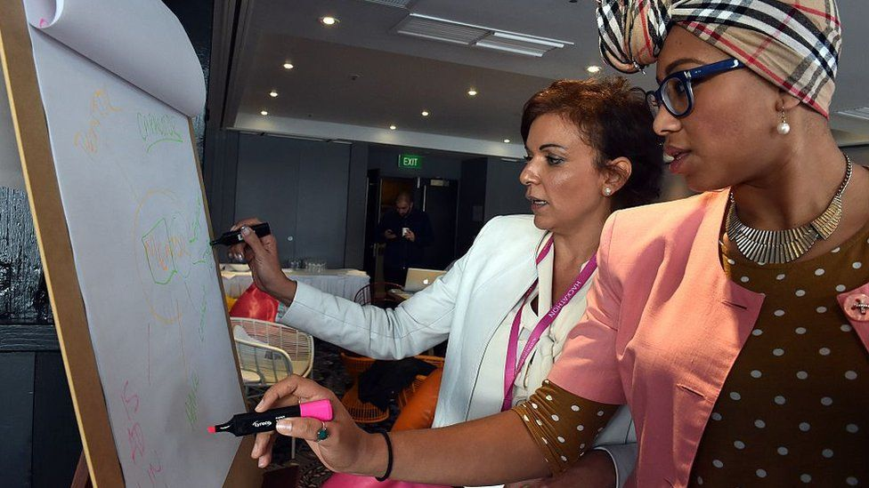 Ms Abdel-Magied stands with a federal MP, Anne Aly, at a summit in 2015