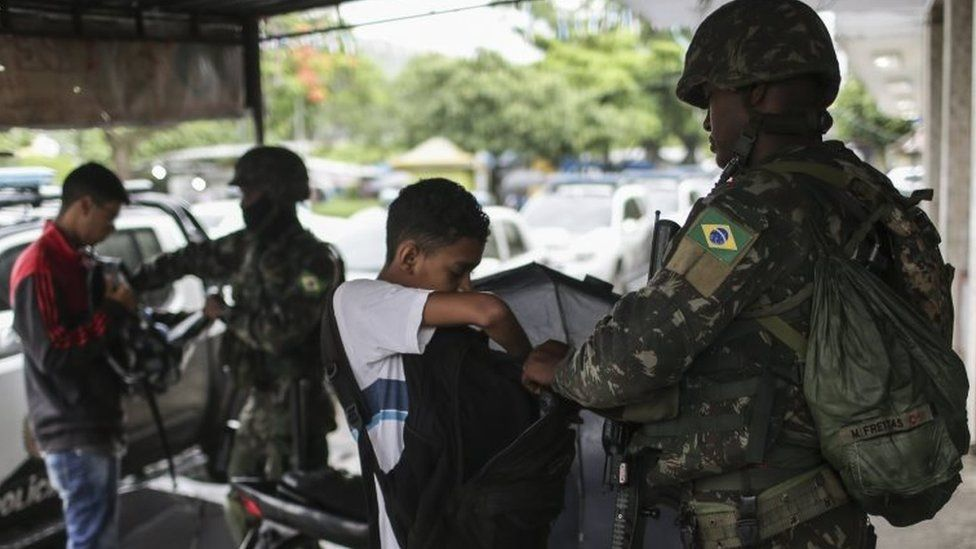 A soldier controls passers-by in Rio de Janeiro, Brazil, 23 February 2018.
