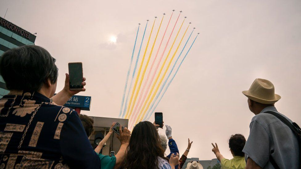 People in the streets of Beijing take photos and wave at planes flying in formation to Tiananmen Square