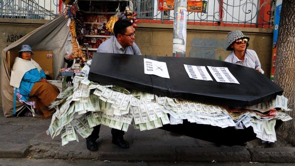 Two people carry a papier-mache coffin filled with paper bills in La Paz