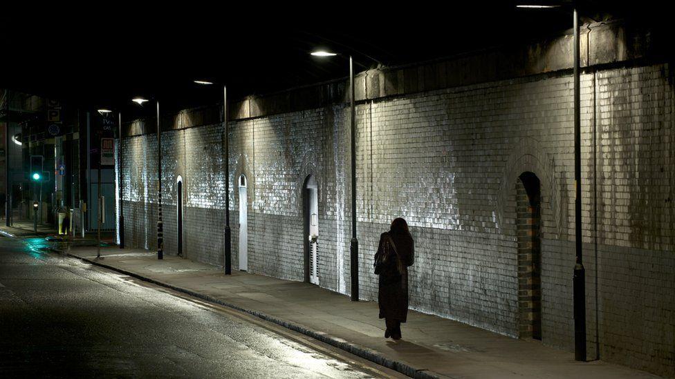 A woman walks alone along a street at night
