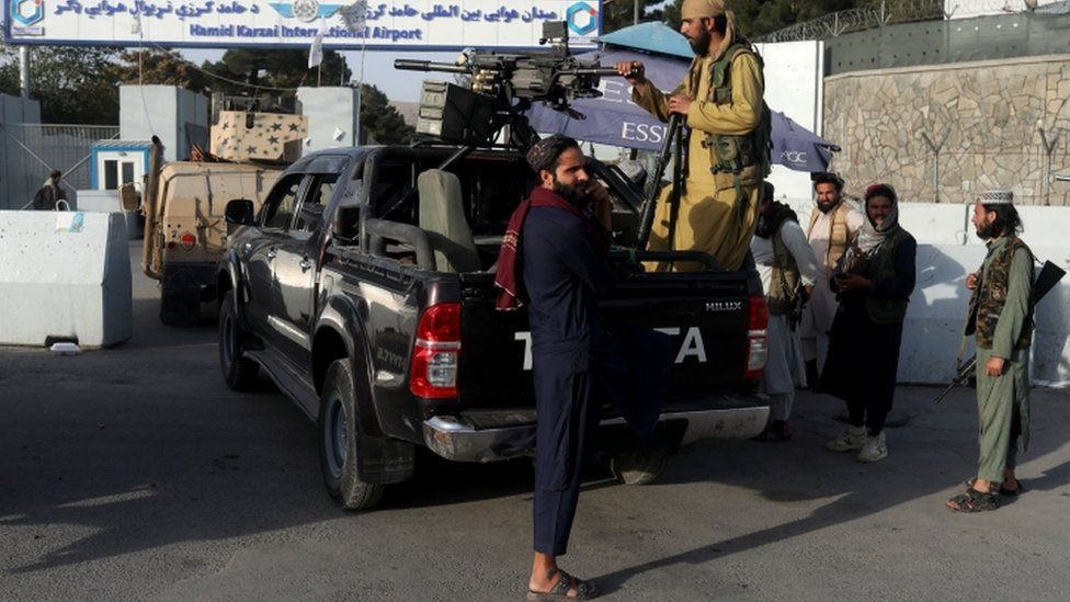 Members of the Taliban guard the entrance to Hamid Karzai International Airport in Kabul, Afghanistan