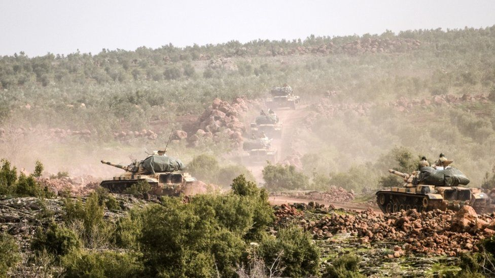 Turkish troops advance near Syrian border throw bush landscape