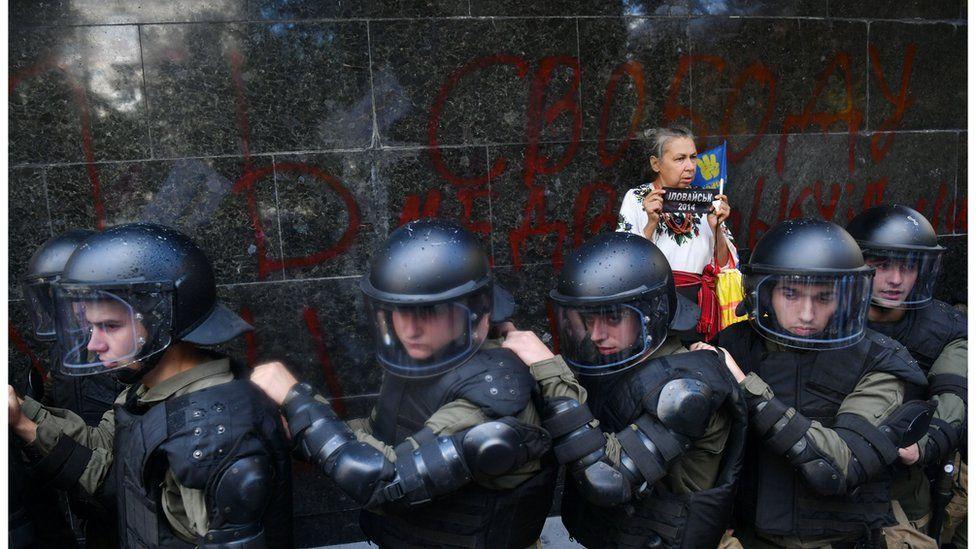 Жінка стоїть біля поліцейського кордону під ГПУ