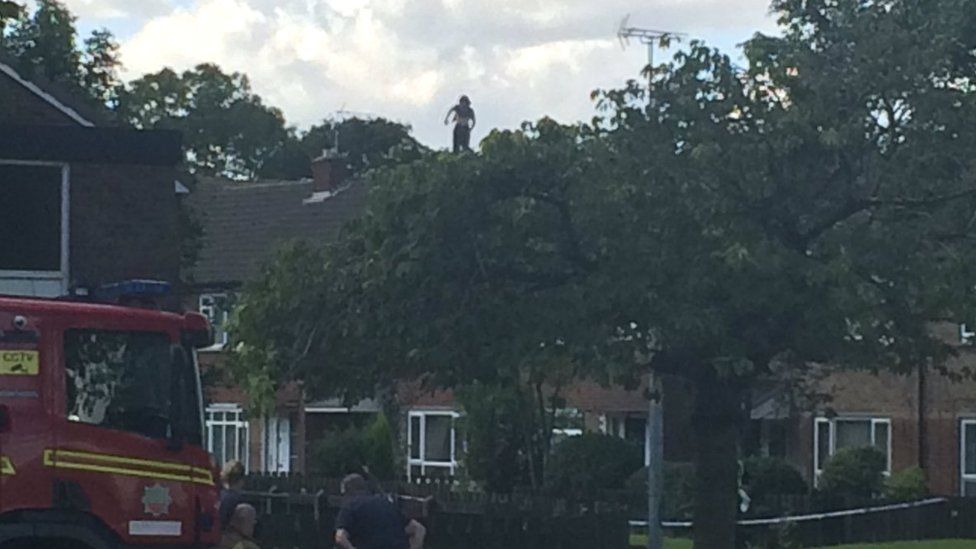 Man on rooftop of a house