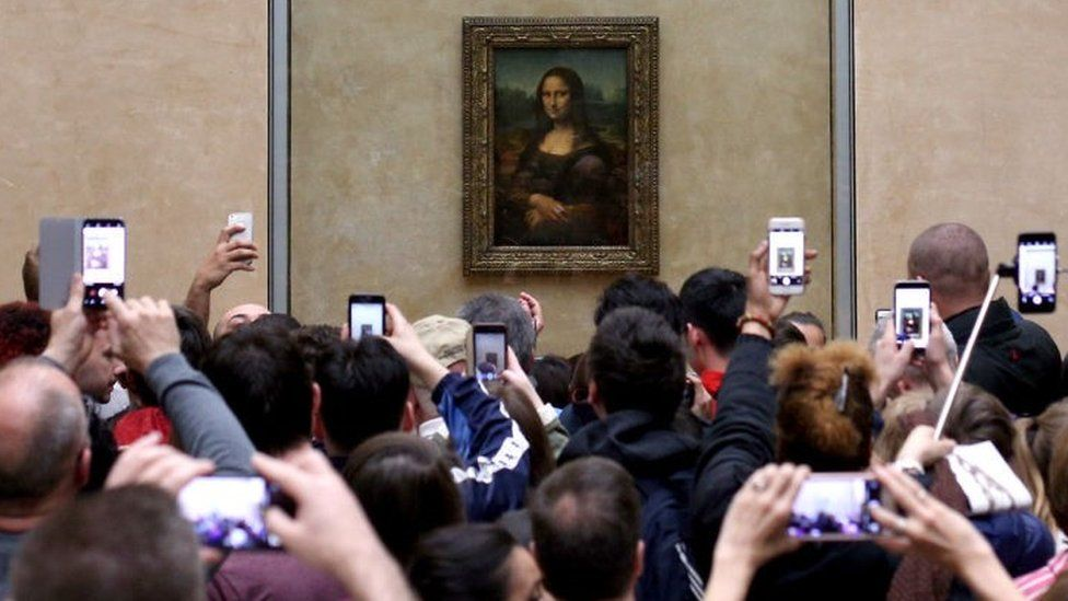 Visitors take pictures of the Mona Lisa by Leonardo Da Vinci, at the Louvre Museum in Paris