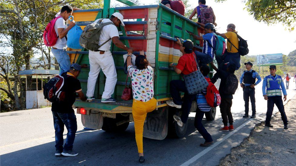 Hondurans climb onto a truck to continue their journey toward the United States