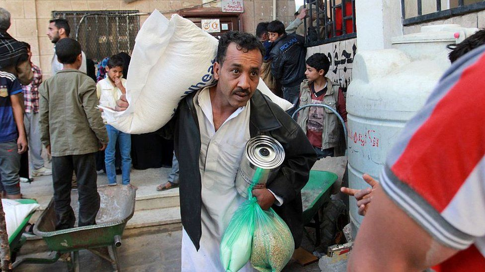 Displaced Yemenis receive food aid distributed by the United Nations in Sanaa on 5 December 2016