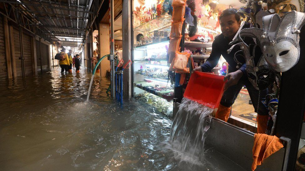 Shopkeeper empties water from his shop in Venice on 29 October 2018