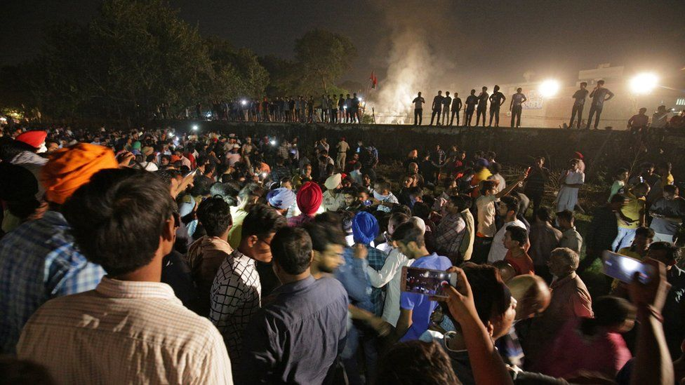People and police gather on the site of a train accident in Amritsar, India, 19 October 2018
