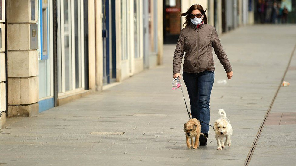 A woman walks two dogs in an empty street