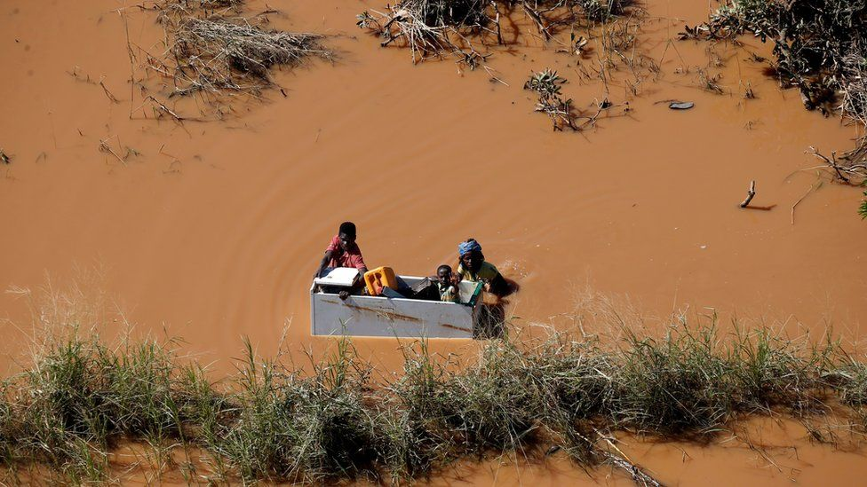 People holding on to some wooden furniture in Mozambique in flooded waters