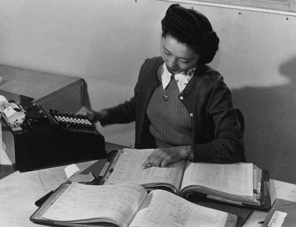 Bookkeeper Teruko Kiyomura pictured in 1943 with various ledgers and an adding machine