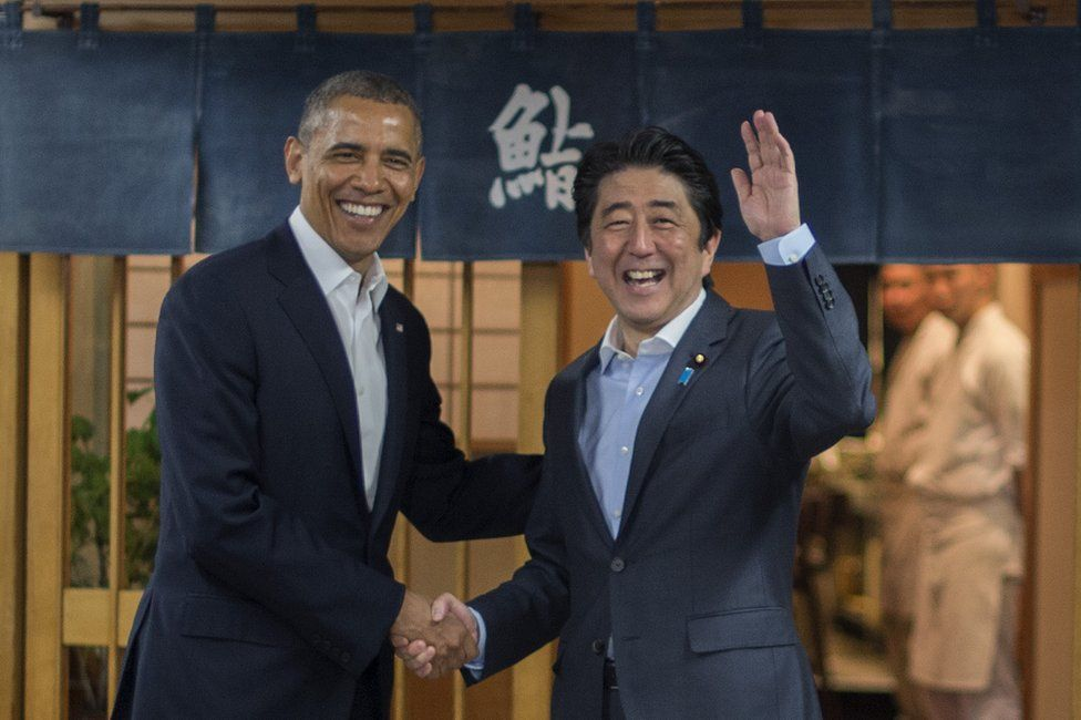 US President Barack Obama (L) shakes hands with Japanese Prime Minister Shinzo Abe before a private dinner at Sukiyabashi Jiro restaurant in Tokyo on 23 April 2014.