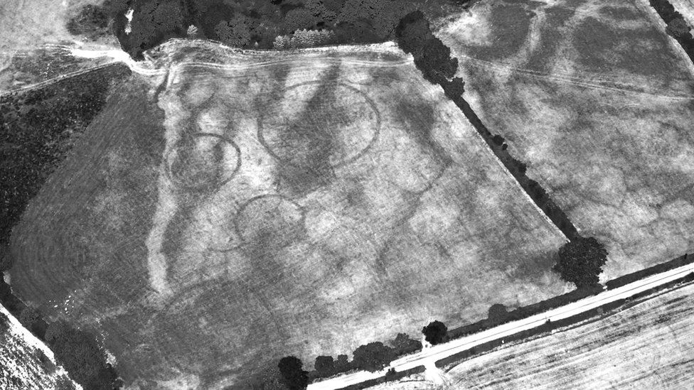 Black and white photograph shows four huge circles or barrows on the ground