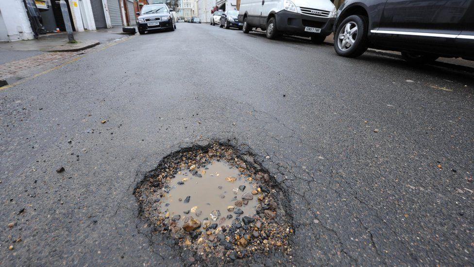 A pothole on a busy urban street