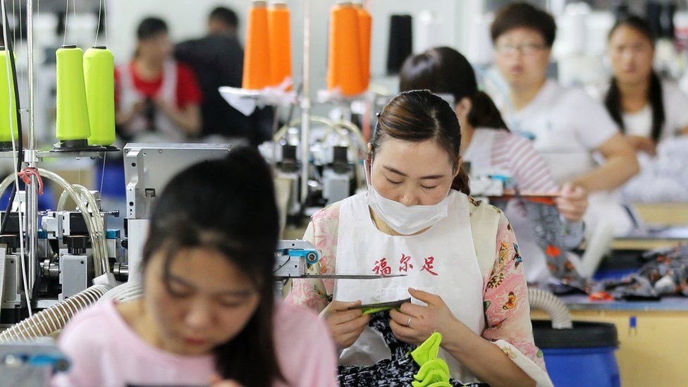 Chinese employees work on socks that will be exported at a factory in Huaibei in China's eastern Anhui province on June 22, 2018.