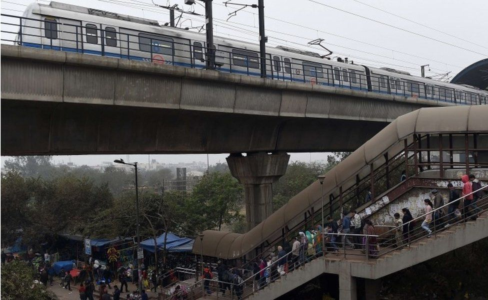 Indian commuters cross a footbridge under a metro trainline in New Delhi on January 15, 2016. N