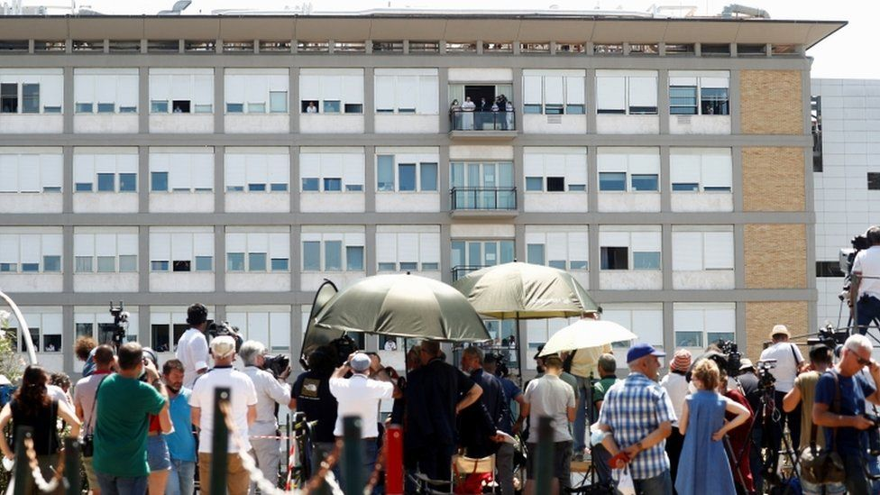 People attend an Angelus prayer led by Pope Francis from a balcony of the Gemelli hospital, as he recovers following scheduled surgery on his colon, in Rome, Italy, July 11, 2021