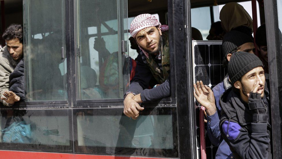 Syrian civilians and rebel fighters evacuated from Harasta, in the Eastern Ghouta, look out of windows in a bus taking them to Idlib province (25 March 2018)