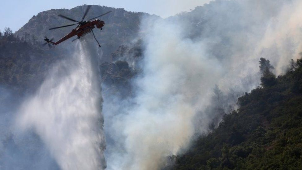 A firefighting helicopter douses a wildfire near Athens