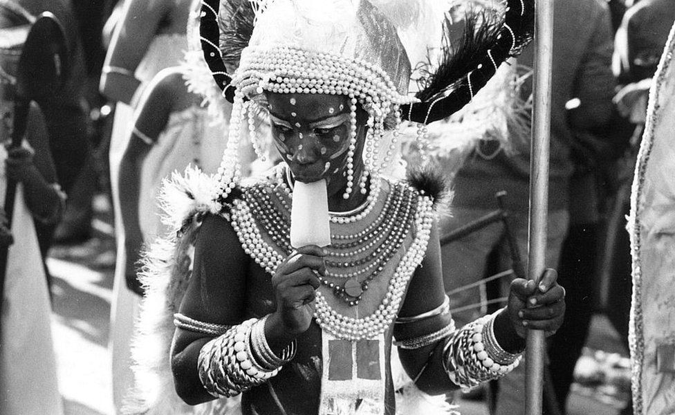 A carnival participant sucks on an ice lolly during the parade at the Notting Hill Carnival in 1980