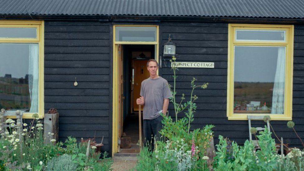 Derek Jarman outside Prospect Cottage