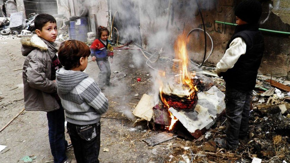 Children warm themselves by a fire in a besieged area of Homs (27 January 2014)