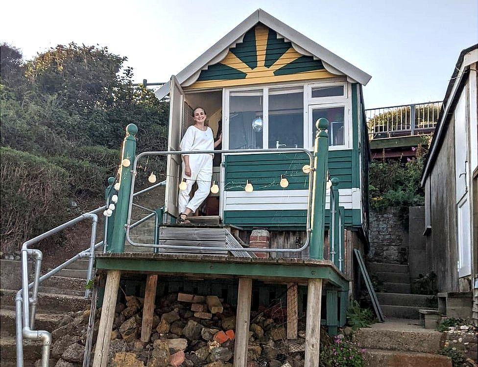 Lauren outside her hut