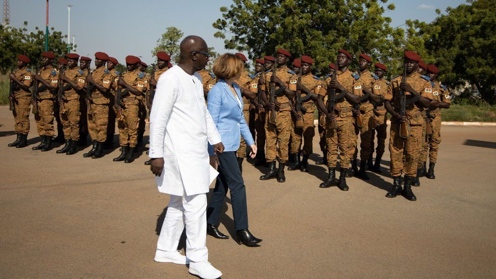 """Cherif Sy, Burkina Faso""""s Defense Minister (L) and Florence Parly, France""""s Defense Minister review the troops during a visit at the Burkinabe minister of Defense in Ouagadougou"""