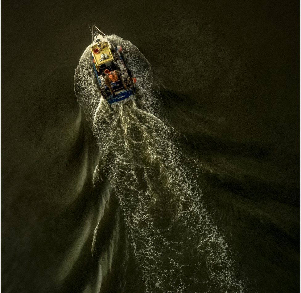 An aerial shot of a fishing boat leaving a trail of disturbance in the water