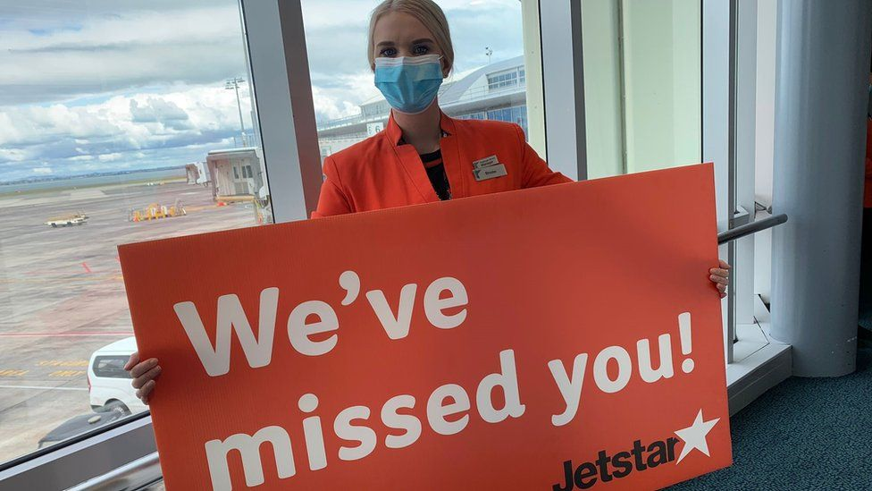 Jetstar crew worker holds sign saying we've missed you