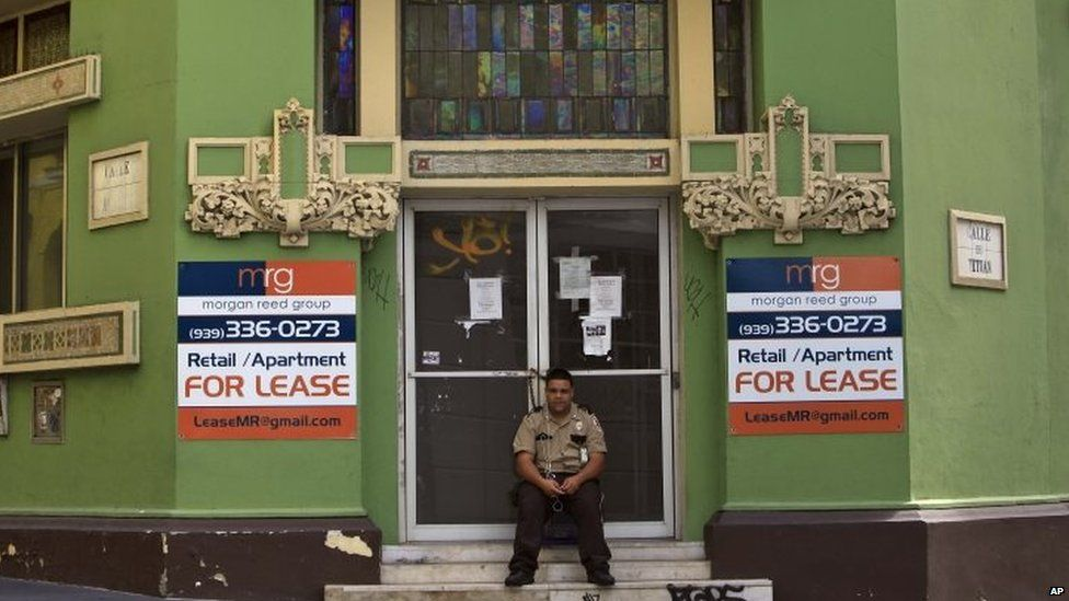 A private security guard sits in front of a closed down business in the colonial district of Old San Juan, Puerto Rico (02 August 2015)
