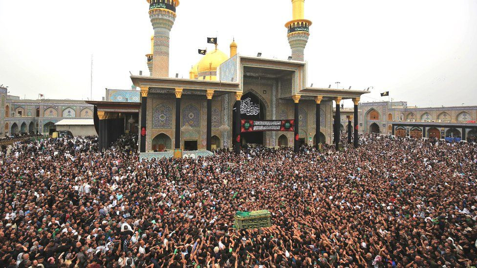 Shiite Muslim worshippers carry a symbolic casket as they gather at the Imam Moussa al-Kadhim's mosque in the Iraqi capital's northern district of Kadhimiya on 12 April, 2018 as they mark the anniversary of the imam's death in the 8th Century.