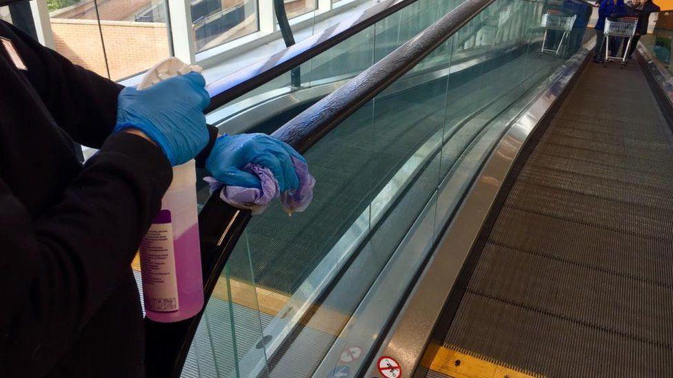 Cleaning handrails in an Edinburgh supermarket