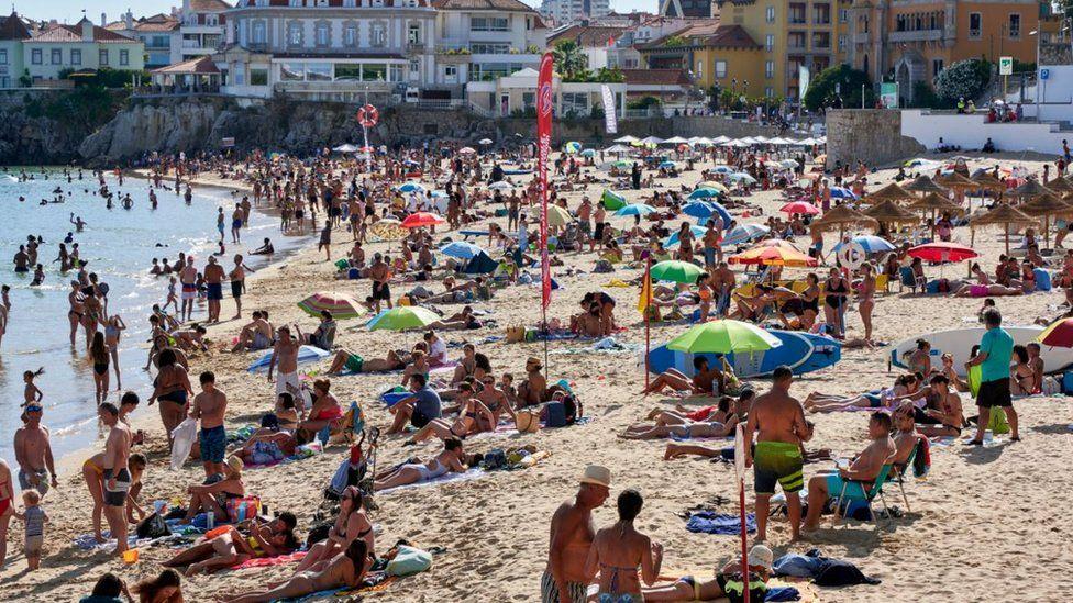 Beachgoers crowd Praia da Duquesa in Cascais, Portugal