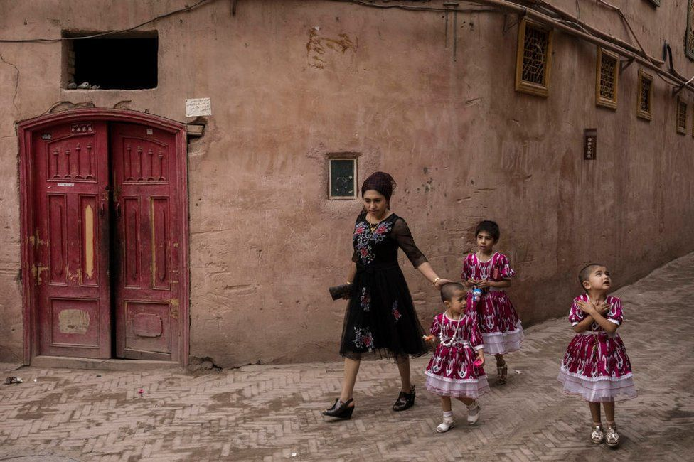An ethnic Uyghur woman walks with her children on June 28, 2017 in the old town of Kashgar, in the far western Xinjiang province, China.