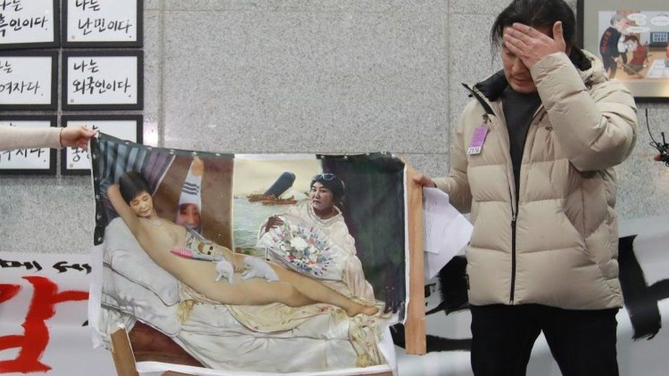 """Artist Lee Koo-Young shows his damaged work """"dirty sleep"""", a painting portraying South Korea""""s President Park Geun-Hye in the nude, after some conservative protesters damaged the artwork during an exhibition of painting parodies in the lobby of the National Assembly building in Seoul on January 24, 2017."""