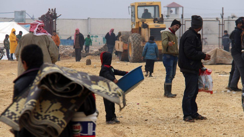 Displaced Syrians fleeing areas in the northern province of Aleppo, gather at the Bab al-Salam camp, outside the town of Azaz (12 February 2016)